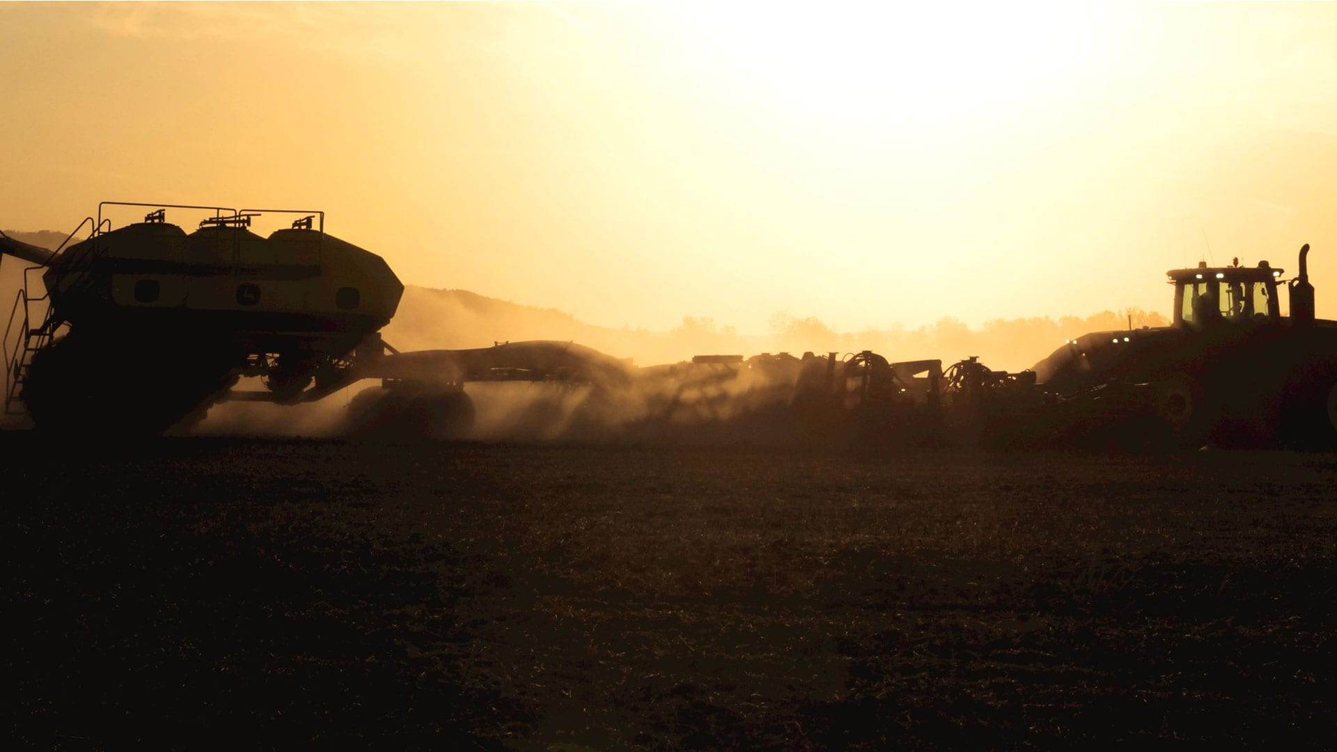 sunrise/sunset of seeding equipment out in the field