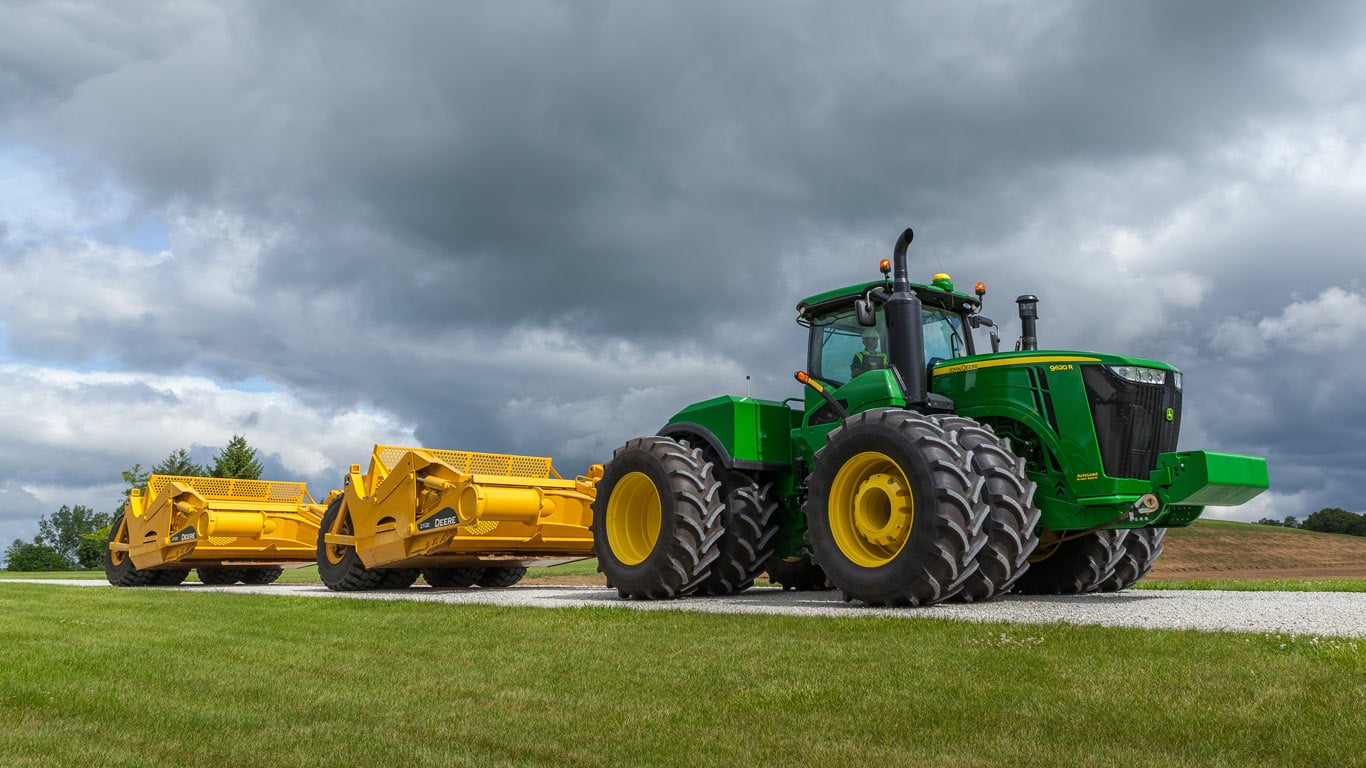 image of dual scrapers attached to tractor on road