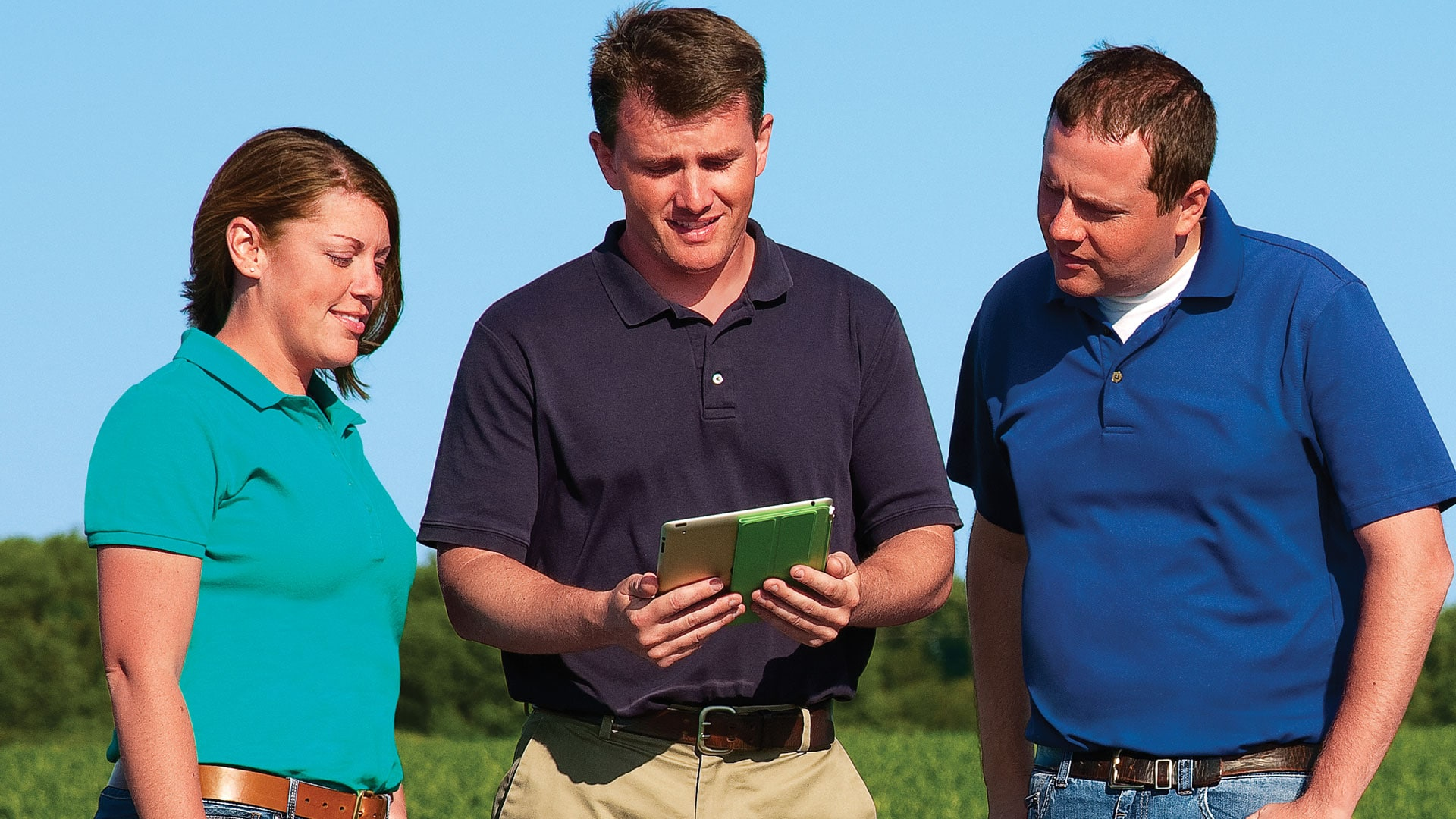 Group standing in field with mobile device