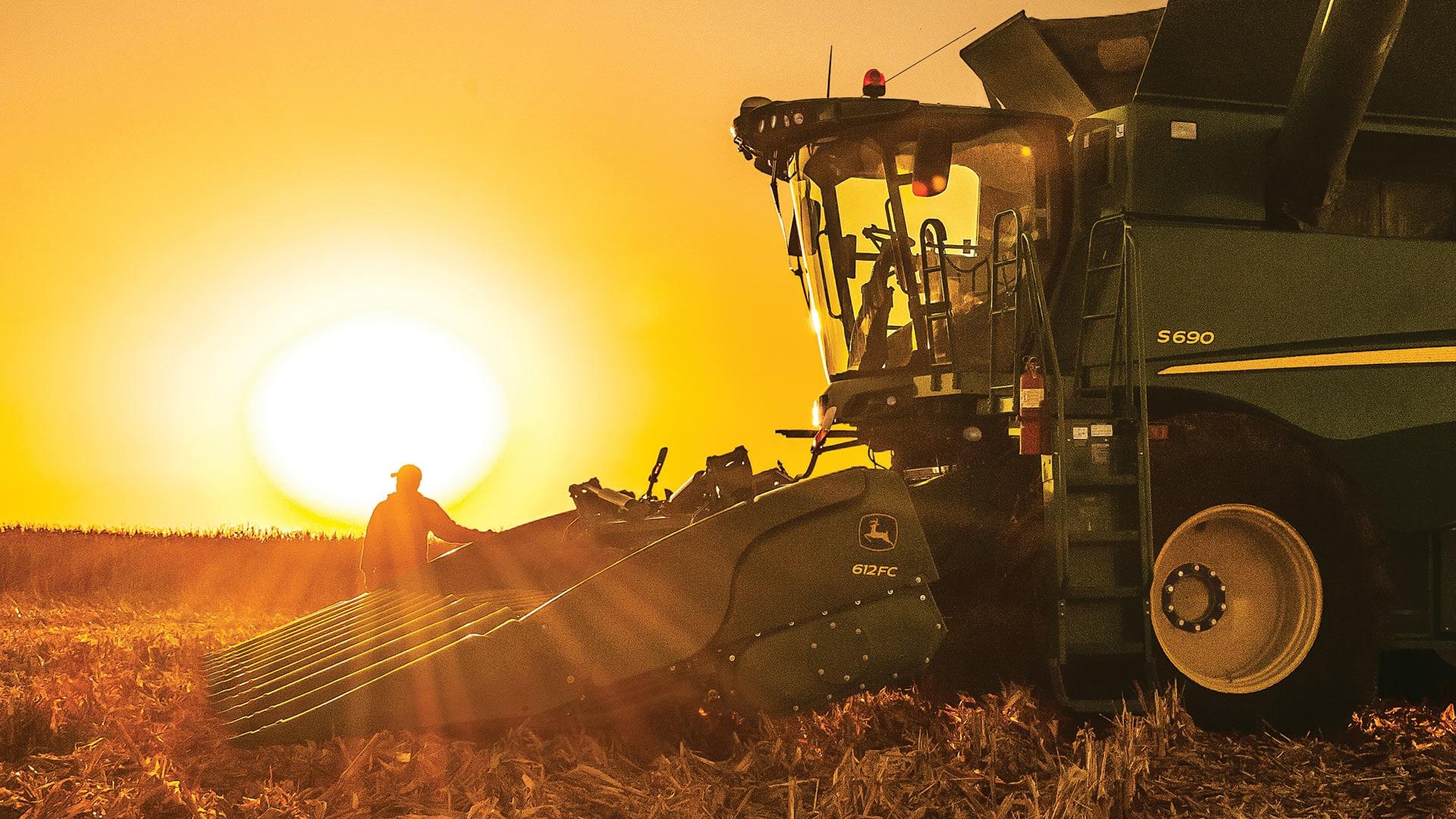 Man operating a John Deere corn head harvester at sunset.